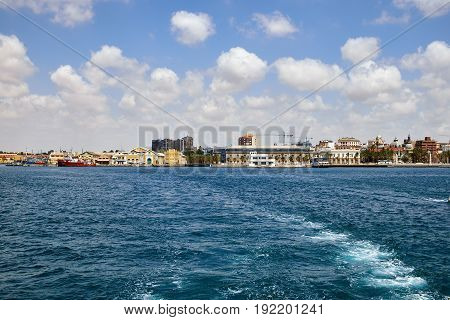 The military area with yellow buildings, in which the entrance is closed. Located in an open area near the port. View of the city from the sea. Cartagena, Spain