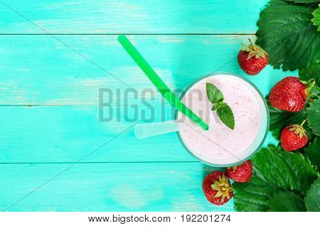 Strawberry-milkshake in a glass on a bright background among berries and green leaves. Top view. Dietary menu. Proper nutrition.