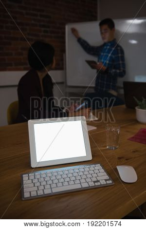 Digital tablet on table while colleague discussing in background at office