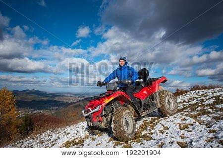 Man On Atv Riding Down From The Snow-capped Peaks On A Sunny Day. Beautiful Mountain Landscape Under