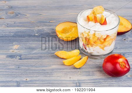 Colorful healthy breakfast with corn flakes ripe slice peach on blue wood board. Decorative border with copy space.