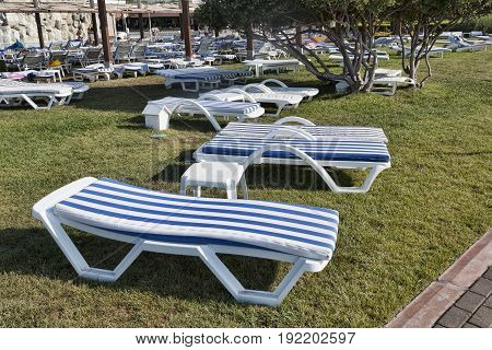 Empty Chaise Lounges With Mattresses On The Lawn At The Hotel In Turkey. Camyuva, Kemer