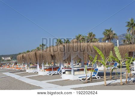 Empty Sunbeds And Gazebos With Salt Roofs On The Beach In Turkey
