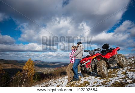 Man Hugging A Woman Near The Red Quad Bike On A Mountain Slope Under The Blue Sky With Cumulus Cloud