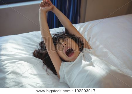 Girl yawning on bed in the bed room at home