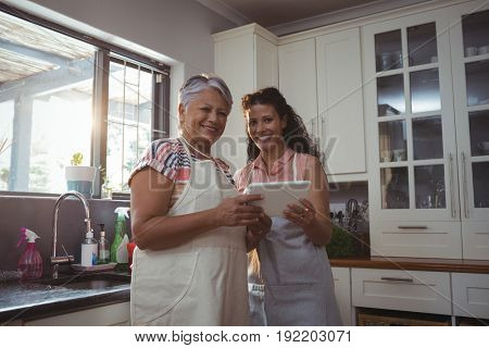 Portrait of mother and daughter using digital tablet in kitchen at home