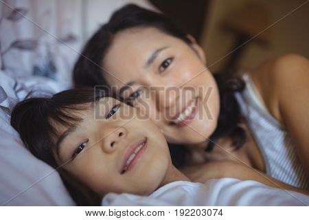 Portrait of mother and daughter relaxing on bed in bed room at home