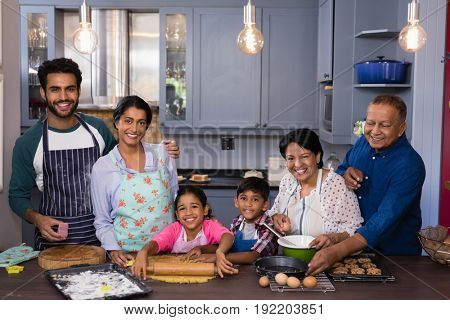Portrait of multi-generation family smiling together while preparing food in kitchen at home