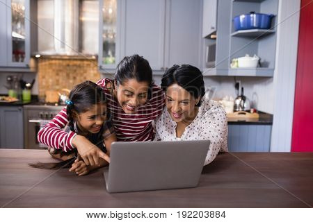 Happy multi-generation family using laptop together in kitchen at home