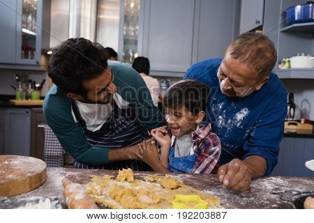 Happy multi-generation family standing together by dough in kitchen at home