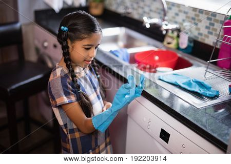 Cute girl wearing glove while standing in kitchen at home