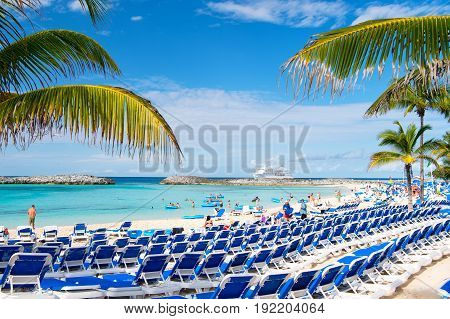 Great stirrup cay Bahamas - January 8 2016: rows of blue lounge chairs on sea beach with white sand green palms people and cruise ship on idyllic skyline. Summer vacation and resort. Paradise