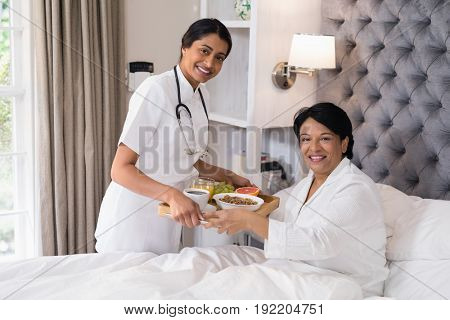 Portrait of smiling nurse serving breakfast to patient resting on bed at home