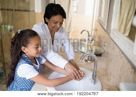 High angle view of grandmother and granddaughter washing hands at bathroom sink