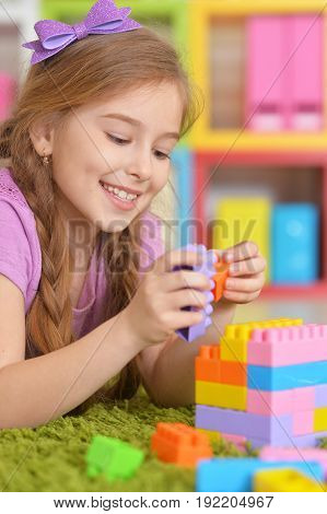 Cute girl playing with colorful plastic blocks in room