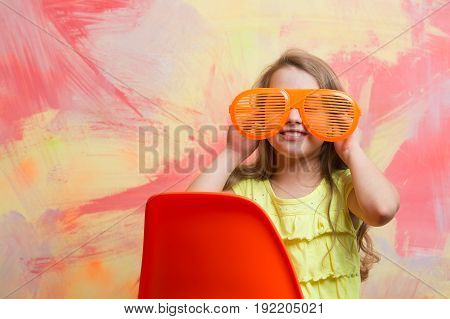 happy child or small girl sitting on orange chair on colorful abstract background in summer glasses and tshirt with long blond hair copy space