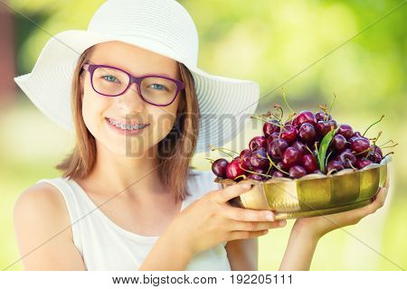 Child with cherries. Little girl with fresh cherries. Portrait of a smiling young girl with bowl full of fresh cherries.