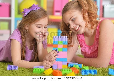 Cute girls playing with colorful plastic blocks in room