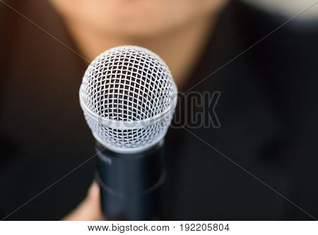 blurred of businessman making speech with microphone and hand gesturing concept for explaining or presentation
