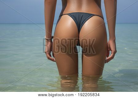 Close-up beautiful luxury slim back of a beautiful woman in a swimsuit posing in the sea water. Sexy tanned body flat stomach perfect figure. Rest on a tropical island. Sexy buttocks. With copyspace