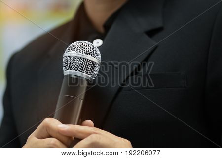 blurred of businessman speech talking with microphone keynote and remote to presentation