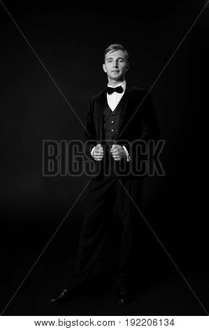 serious fashionable handsome man in black tuxedo suit and bow tie on black background