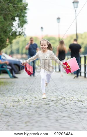 Pretty Little Girl Running On Street With Pink Shopping Bags