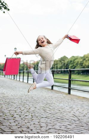 Pretty Little Girl Jumping On Street With Pink Shopping Bags