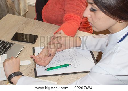 Closeup of doctor checking heartbeat and pulse on patient's wrist. Health care. Doctor and patient