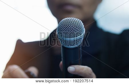 reporter offers someone to give her an interview. Holding microphone and remote in her hand.