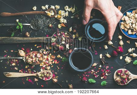Chinese black tea in black stoneware cups, man's hand holding one cup and wooden spoons with herbs, flower buds and leaves over black wooden background, top view