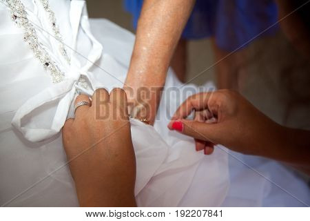 witness help clothing bride in wedding day with corset