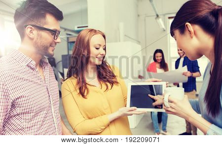 business, communication, startup and people concept - happy multiracial creative team or students with tablet pc computer on coffee break talking at office