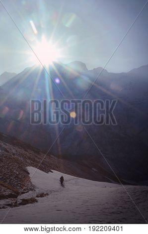 Sunbeams and traveler silhouette in Himalayan mountains. Nepal, Annapurna region, Annapurna Base Camp track.