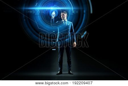 business, technology and people concept - businessman in suit touching virtual projection over black background