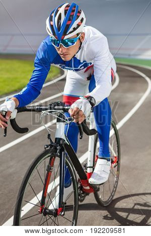 Young professional cyclist on a velodrome outdoor