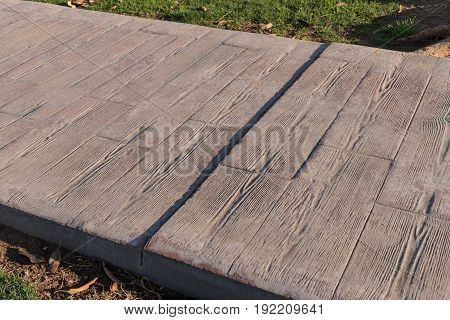 stamped concrete pavement outdoor with expansion joint working, Wooden slats pattern, flooring exterior, decorative texture of cement paving with streaks of wood
