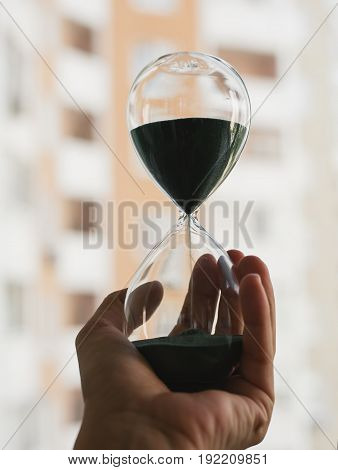 Hourglass sand glass infemale hand over city