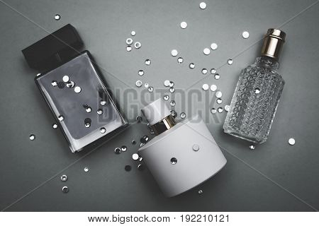 Three bottles of female perfume over grey