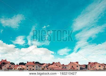 Row of new townhouses on the background of blue sky. The facades of the buildings the front view. Construction business and sale. Urban landscape.