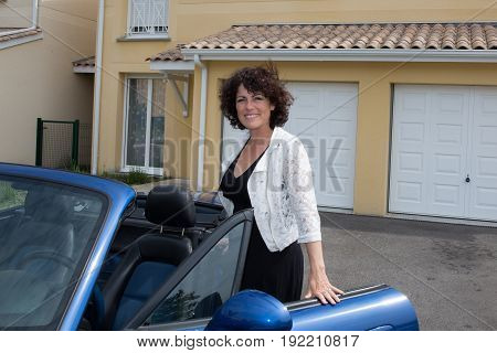Beautiful Home With Two Garages And Woman Go In Convertible Blue Car