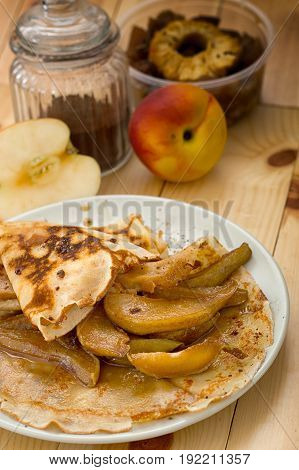 Pancakes with caramel pears. Rustic style. Wooden background. Close-up. Top view