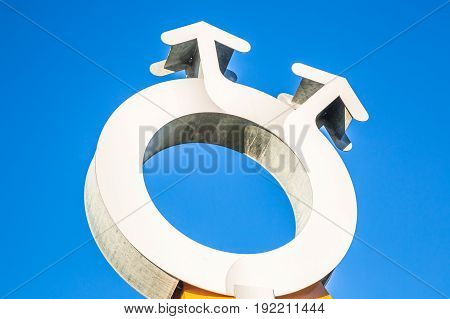 Bologna, Italy - December 28, 2016: Close up od outdoor sculpture with homosexual couple symbol in the blue sky. Freedom, relationships, love and homosexuality concept.