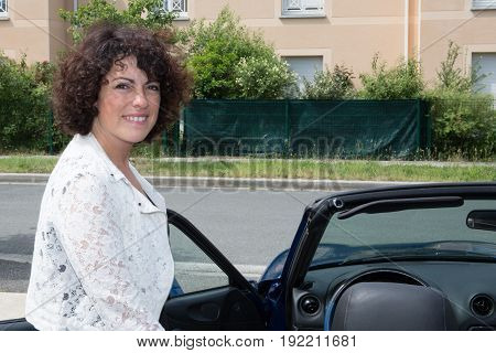 Curly Brunette Woman With Car In City Street