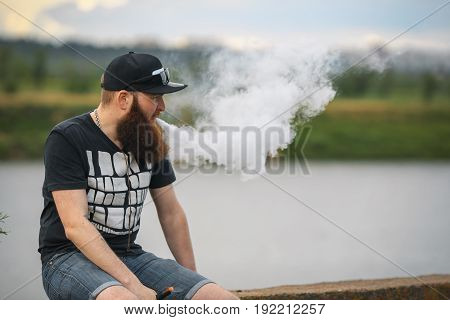 Vape Bearded Man In Real Life. Portrait Of Young Guy With Large Beard In A Cap And Sunglasses Having