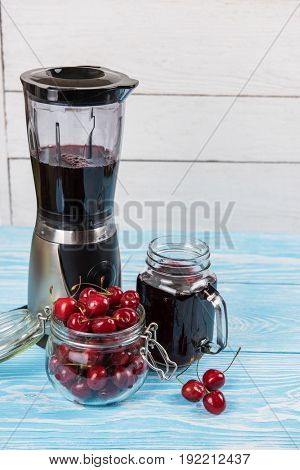 Cherry juice with glass jar,of berries, blender and juice on blue wooden background