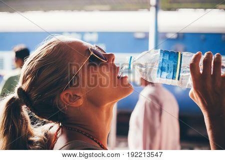 Beautiful girl having fun drinking water outdoors close-up portrait. A girl in India traditionally drinks clean water from a bottle. Concept - water ecology thirst.