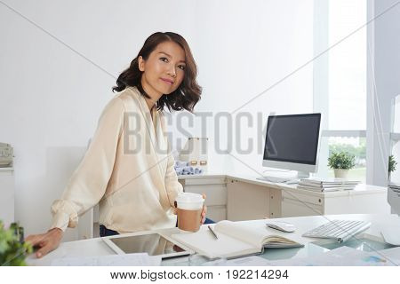 Portrait of young Asian businesswoman posing at workplace with paper coffee cup