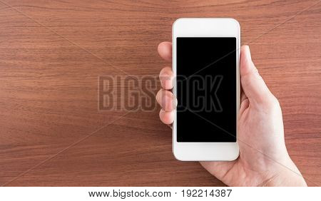 Hand Holding Empty Screen Of Mobile Phone Above Brown Table Top View, Leave Space For Display Of You