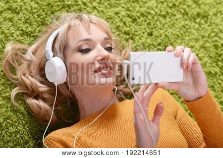 Beautiful young woman listening music in headphones while lying on green grass